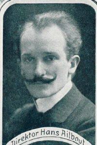 Der Kompomist Hans Ailbout ist hier dargestellt, er trägt einen Anzug und guckt geradeaus